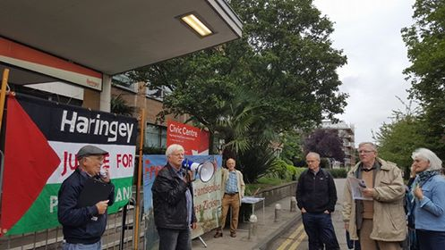 Professor Haim Bresheeth addresses the protest outside the Council Meeting, in front of the FSOI banner